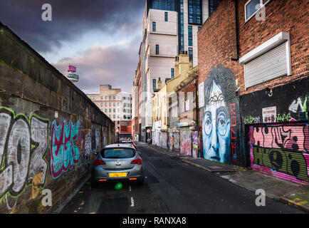 A moody scene of the back alley of Cropper Street, Liverpool with a John Lennon mural and other graffiti. - Stock Image