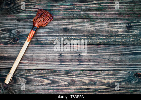 BBQ Mop or brush over top a rustic wood table / background with barbecue sauce on end. Image shot from overhead view. - Stock Image