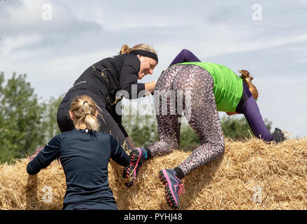 A woman helping a friend over a straw bale wall - Stock Image