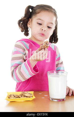 Stock image of little girl eating chocolate chip cookies and milk over white background - Stock Image