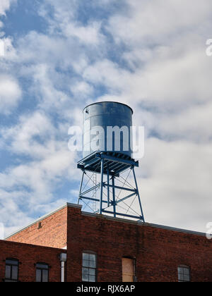 Blue roof top water tower or tank on top of a brick building in downtown Montgomery Alabama, USA. - Stock Image