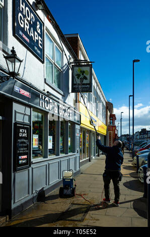 Man cleaning the outside of the Hop and Grape public house Redcar using an extendable Window Cleaner Telescopic Pole and brush - Stock Image
