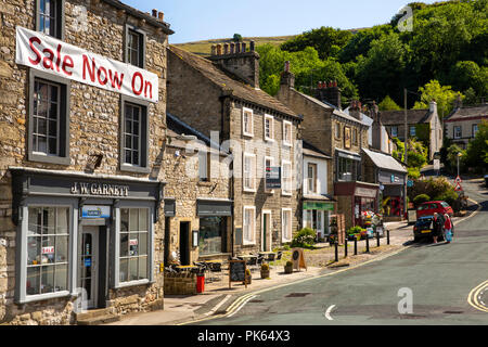UK, Yorkshire, Settle, Market Place, shops beside road to Constitution Hill - Stock Image