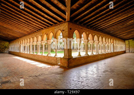 Moissac Abbey monastery courtyard in Moissac. View of the of archways that lines the yard as seen from one corner, under late pm sun. Moissac, France, - Stock Image