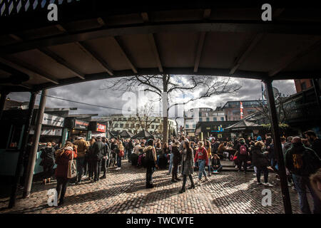 tree and tourists in outdoor food court ,camden lock market ,london. - Stock Image