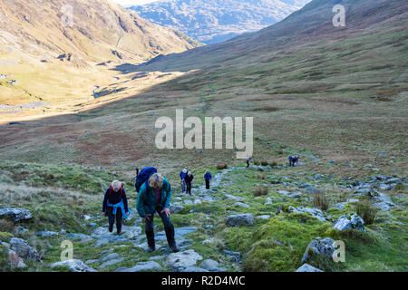 Hikers hiking up path from Cwm Llan on slopes of Yr Aran mountainside in Snowdonia National Park. Bethania, Gwynedd, Wales, UK, Britain - Stock Image