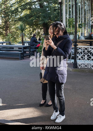 Two pretty asian girls looking at a smart phone and laughing, in a parkland setting. - Stock Image