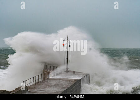 Porthleven, Cornwall, UK. 28th November 2018. UK Weather. Winds gusting over 60mph  from Storm Diana, pushing huge waves over the breakwater at Porthleven this morning. Credit: Simon Maycock/Alamy Live News - Stock Image