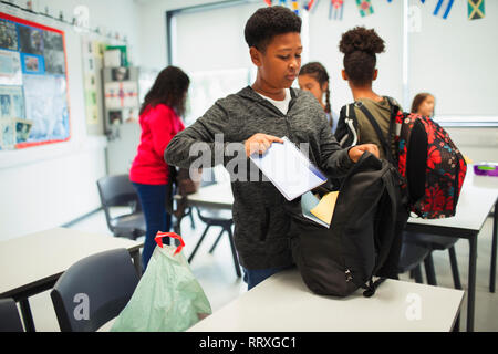 Junior high school boy placing notebook in backpack in classroom - Stock Image