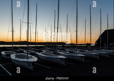 Schull, West Cork, Ireland. 18th Oct, 2018. The orange glow of sunrise through the sailing dinghies of Schull Harbour Sailing Club. The day will be dry and bright with sunny spells and temperatures of 11 to 14°C. Credit: Andy Gibson/Alamy Live News. - Stock Image