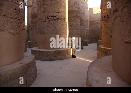 Egypt, Luxor, Karnak, The Great Temple of Amun, Great Hypostyle Hall. Man in traditional dress. - Stock Image
