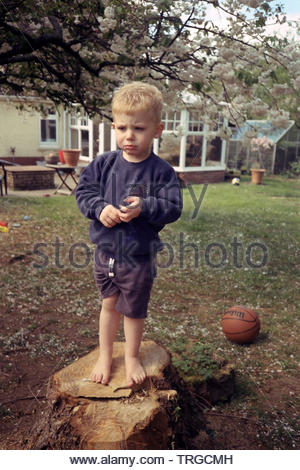 Grumpy two year old boy in the garden, Medstead, Alton, Hampshire, England, United Kingdom. - Stock Image