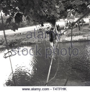 1960s, historical, a young adventure scout crosses a river on a rope bridge, tied to a tree on the riverbank, England, UK. - Stock Image