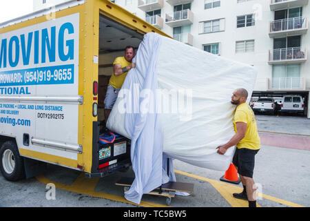 Miami Beach Florida moving van company movers king size mattress Hispanic man employee working job teamwork lifting loading - Stock Image