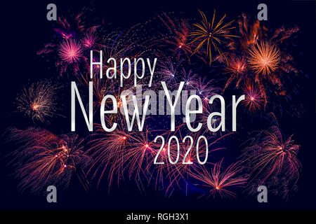 Happy New Year 2020 greeting with colorful fireworks in the night sky - Stock Image