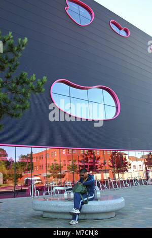 Black lady sitting on a bench in front of The Public by Will Alsop, now part of Sandwell College, West Bromwich - Stock Image