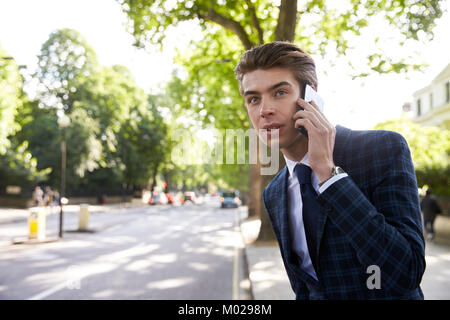 Young businessman on phone in the street, waiting for taxi - Stock Image