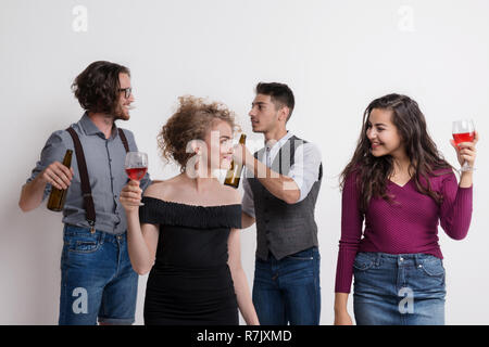 Portrait of young group of friends standing in a studio, holding bottles and glasses with drink. - Stock Image