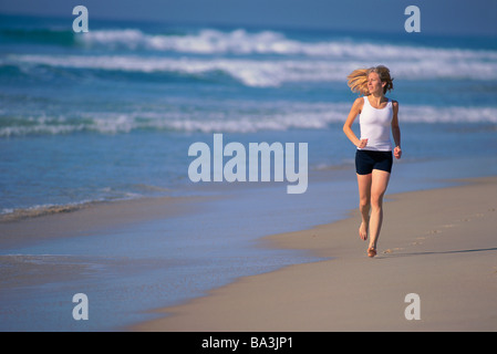 Young woman jogging along beach - Stock Image
