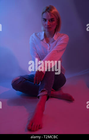 Girl in blue jeans and bare feet sitting down in studio with colorful blue and red lights. Fashion sexy woman posing and low key light  setup - Stock Image