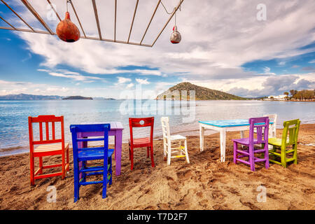 Colorful retro wooden chairs and a table lined up on the beach at the seaside in Gumusluk, Bodrum, Turkey. - Stock Image