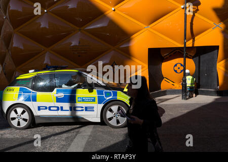 A Zero Emission BMW i3 Met Police patrol car drives past the temporary renovation hoarding of luxury brand Louis Vuitton in New Bond Street, on 25th February 2019, in London, England. - Stock Image