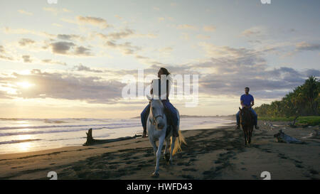 Couple riding horses on remote ocean beach under sunset sky - Stock Image