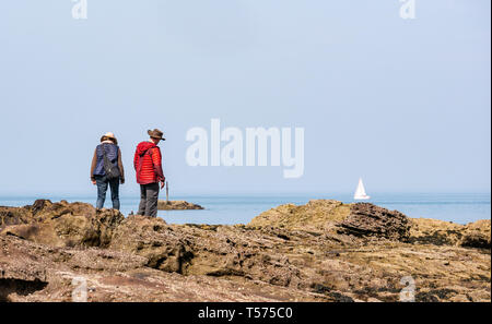 Dunbar, East Lothian, Scotland, UK. 21st Apr 2019. UK Weather:  People enjoy the very sunny hot Easter day weather at Eye Cave cove. A couple admire the sea view on the rocky shore with a sailing boat in the sea - Stock Image