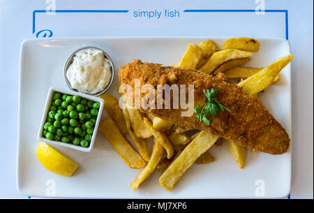 A dish of plaice and chips with peas and tartare sauce, Pier One fish restaurant, Connaught Avenue, Frinton-on Sea, Essex, England - Stock Image