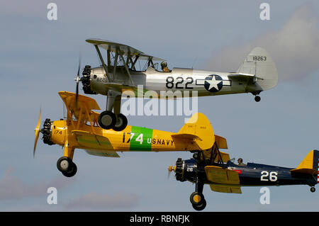 Three Boeing Stearman biplanes flying in formation. Biplane training planes. Second World War biplanes. Flying at an airshow. Space for copy - Stock Image