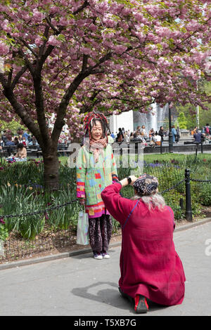 A man takes a cell phone photo of his Asian companion under a Cherry Blossom tree in Washington Square Park in Greenwich Village, New York City. - Stock Image