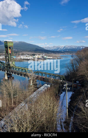 Train crossing CN railway bridge at Second Narrows of the Burrard Inlet in Vancouver, BC, Canada.   Train crossing bridge to North Vancouver in Winter - Stock Image