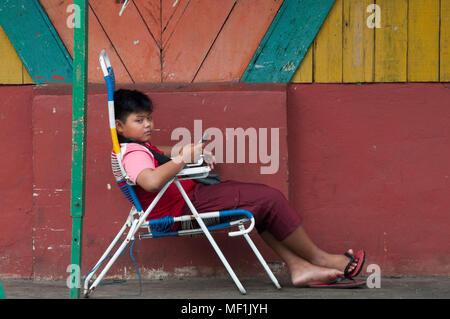 Boy relaxing outside a shed at the Night Market, Kota Kinabalu, Sabah - Stock Image
