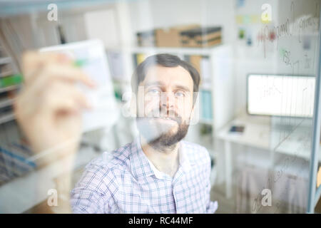 Confident office manager or economist standing by transparent board and sketching rating chart with highlighter - Stock Image