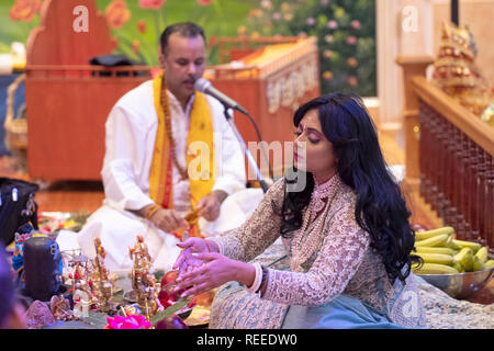 A beautiful devout Hindu worshipper celebrates her birthday by assisting in the morning prayer service. In Richmond Hill, Queens, New York City. - Stock Image