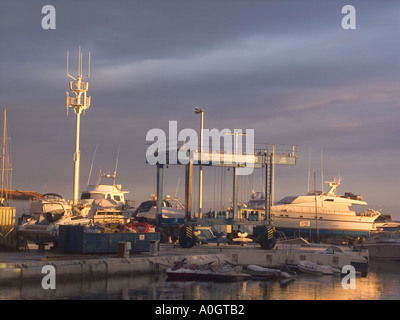 Puerto Banus, Costa del Sol , Spain, dusk evening light boatyard boatyards sunset sunsets buildings playground of the rich yacht - Stock Image