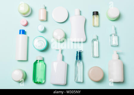 Group of plastic bodycare bottle Flat lay composition with cosmetic products on blue background empty space for you design. Set of White Cosmetic cont - Stock Image