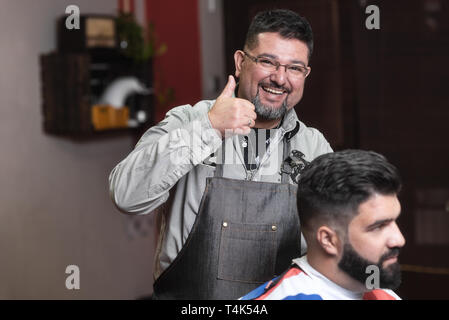 Happy barber customer satisfied with the result. Barber smiling showing thumb up . - Stock Image