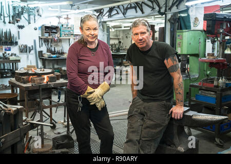 Two blacksmiths, a Caucasian man and woman, in their workshop. - Stock Image