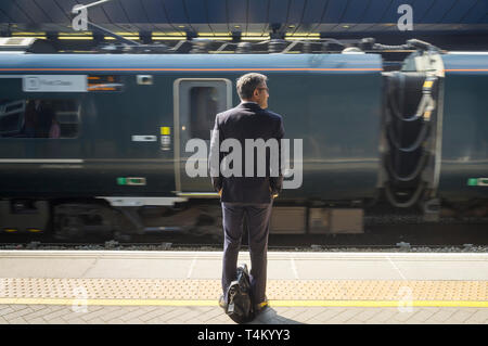 A commuter with a briefcase waits on the platform at Reading Station, Berkshire - Stock Image