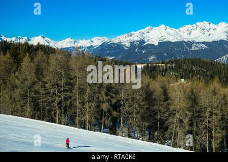 One skier on the snow mountain slopes. landscape with beautiful conferous forest and blue sky. Kronplatz, Dolomites, South Tyrol, Italy. - Stock Image