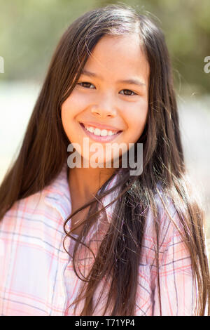 Portrait of a young mixed race girl smiling outside. - Stock Image