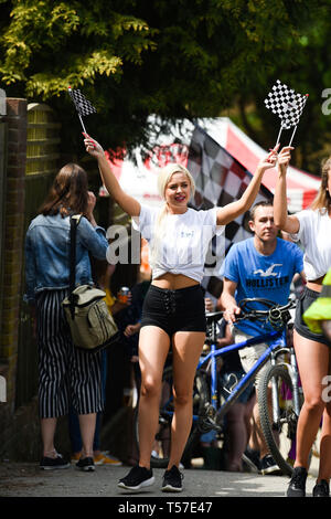 Bolney Sussex, UK. 22nd Apr, 2019. A promotion lady leads competitors in the annual Bolney Pram Race in hot sunny weather . The annual races start and finish at the Eight Bells Pub in the village every Easter Bank Holiday Monday Credit: Simon Dack/Alamy Live News - Stock Image