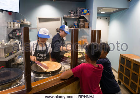 Two boys watching women make crapes, Kahala Mall, Honolulu, Oahu, Hawaii, USA - Stock Image