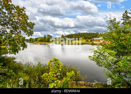 Boats docked at the Porvoonjoki river adjacent to the medieval village and homes of Porvoo, Finland in early autumn - Stock Image