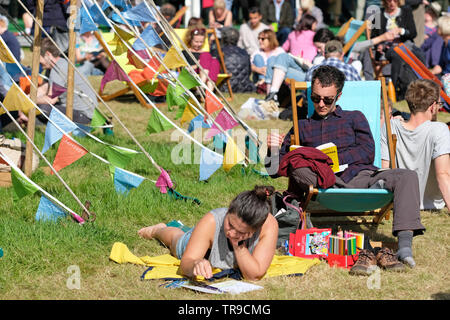 Hay Festival, Hay on Wye, Powys, Wales, UK - Friday 31st May 2019 - Visitors enjoy a break between events on the Festival lawns as the sun emerges on Friday afternoon. Photo Steven May / Alamy Live News - Stock Image
