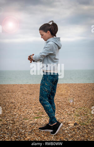 woman runner checking her fitbit, smart watch, - Stock Image