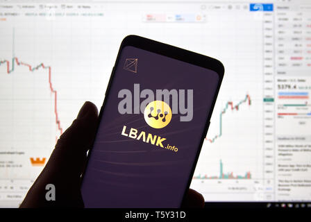 MONTREAL, CANADA - APRIL 26, 2019: Lbank cryptocurrency exchange logo and application on Android Samsung Galaxy s9 Plus screen in a hand over a laptop - Stock Image