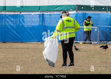 A litter picking up litter at an outdoor event wearing high-vis clothing - Stock Image