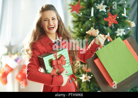 smiling young woman in red trench coat with shopping bags and Christmas present box near Christmas tree - Stock Image
